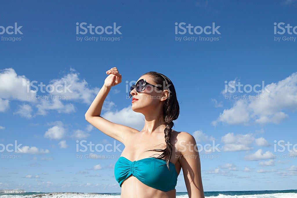 Woman on beach wearing sunglasses stock photo
