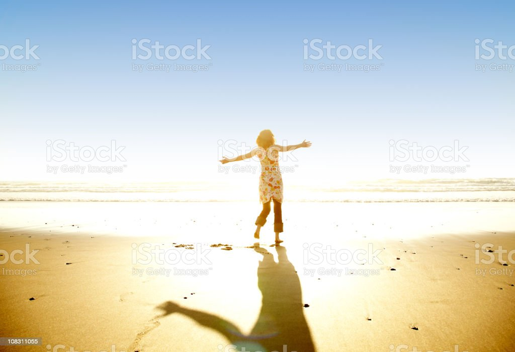 Woman on Beach With Arms Outstretched stock photo