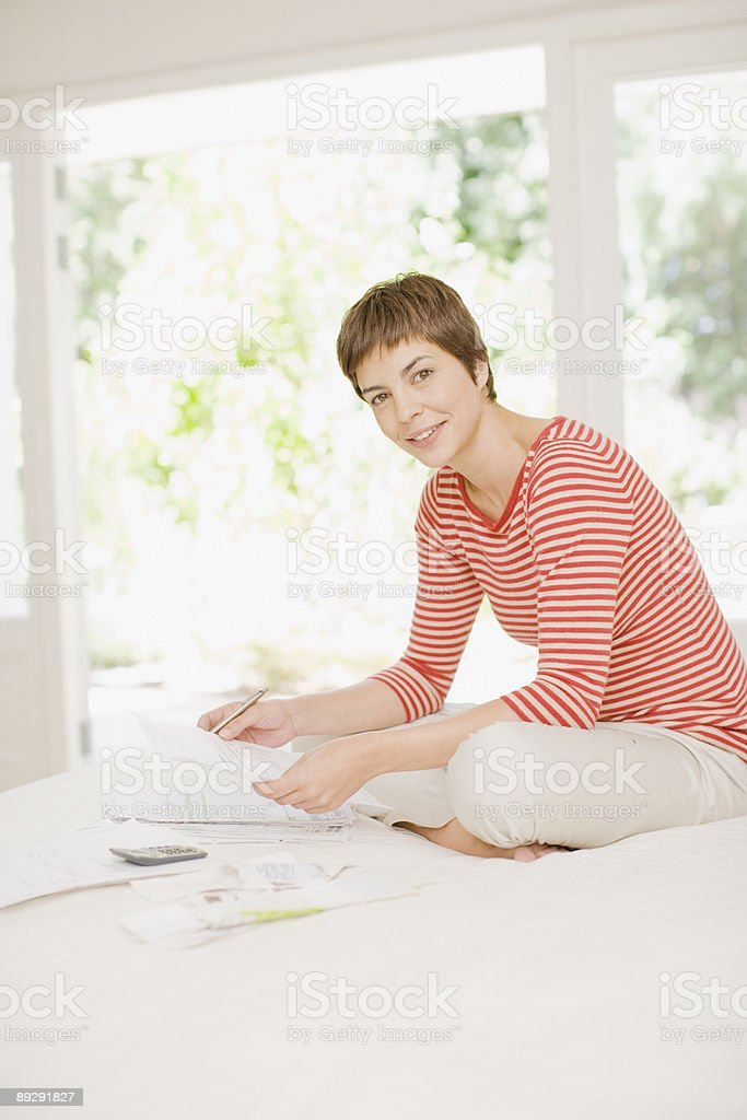 Woman on bed paying bills royalty-free stock photo