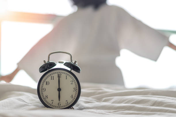 Woman on bed wake up stretching in bedroom with alarm clock at 6.00 a.m. morning. Biological Clock healthcare concept. Woman on bed wake up stretching in bedroom with alarm clock at 6.00 a.m. morning. Biological Clock healthcare concept. AM stock pictures, royalty-free photos & images