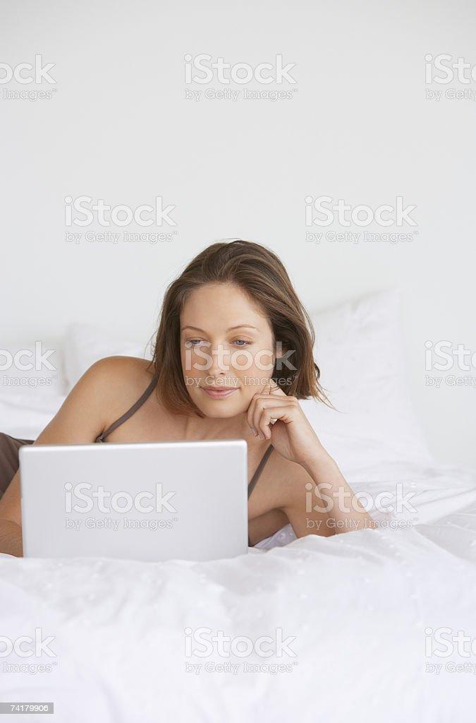 Mulher na cama com computador portátil foto de stock royalty-free