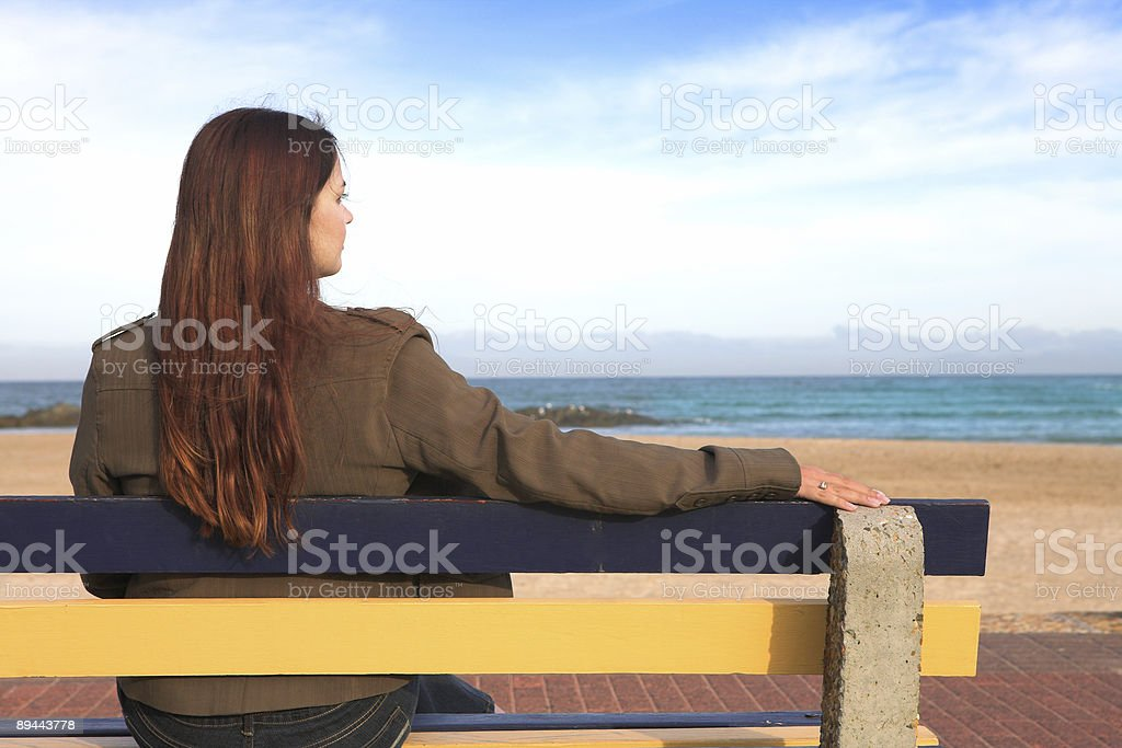 Woman on bench next to sea royalty-free stock photo