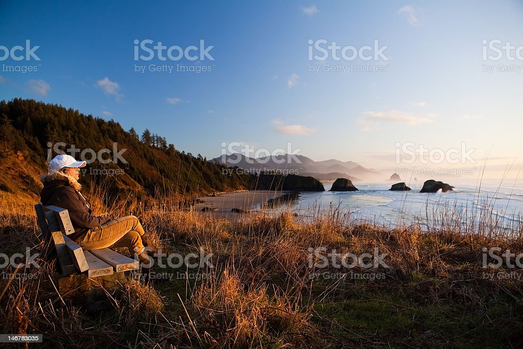 woman on bench overlooking coast stock photo