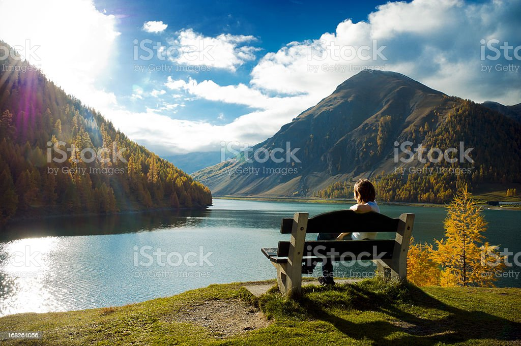 Woman on bench overlooking lake and mountains royalty-free stock photo