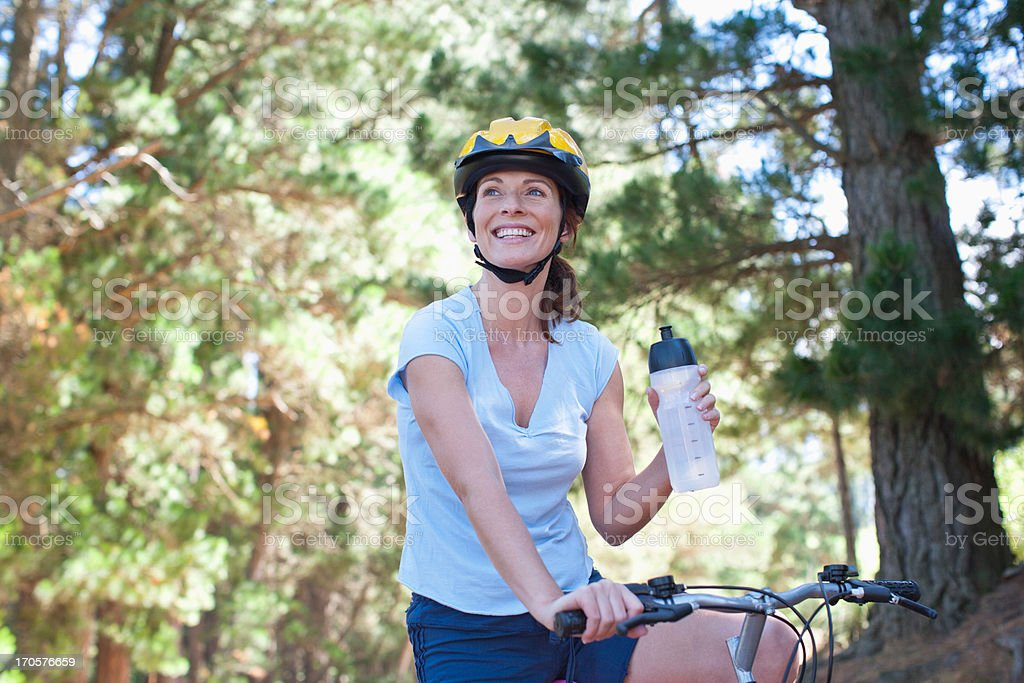 Woman on bicycle drinking water in forest stock photo