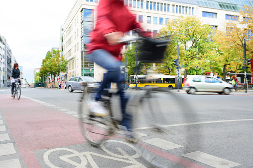 Berlin, Germany - September 5, 2015: Motion blurred woman on bicycle. In bike lane. Scene from central Berlin.