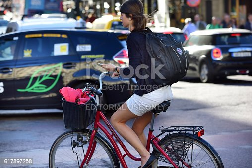 863454090 istock photo Woman on bicycle in profile, with phone 617897258