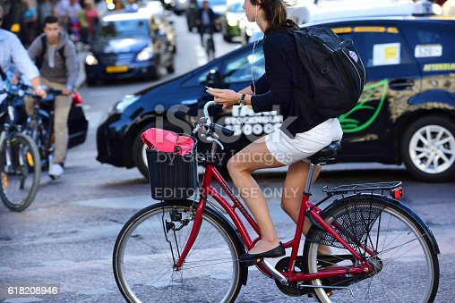863454090 istock photo Woman on bicycle in profile, with phone 618208946