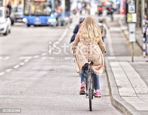 583973114istockphoto Woman on bicycle in traffic, bus in background 622805098