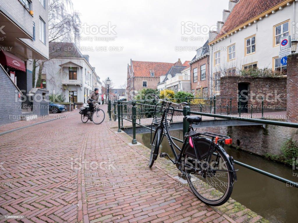 Vrouw op fiets passeert andere fietsen in smalle middeleeuwse straat in de stad amersfoort in Nederland foto