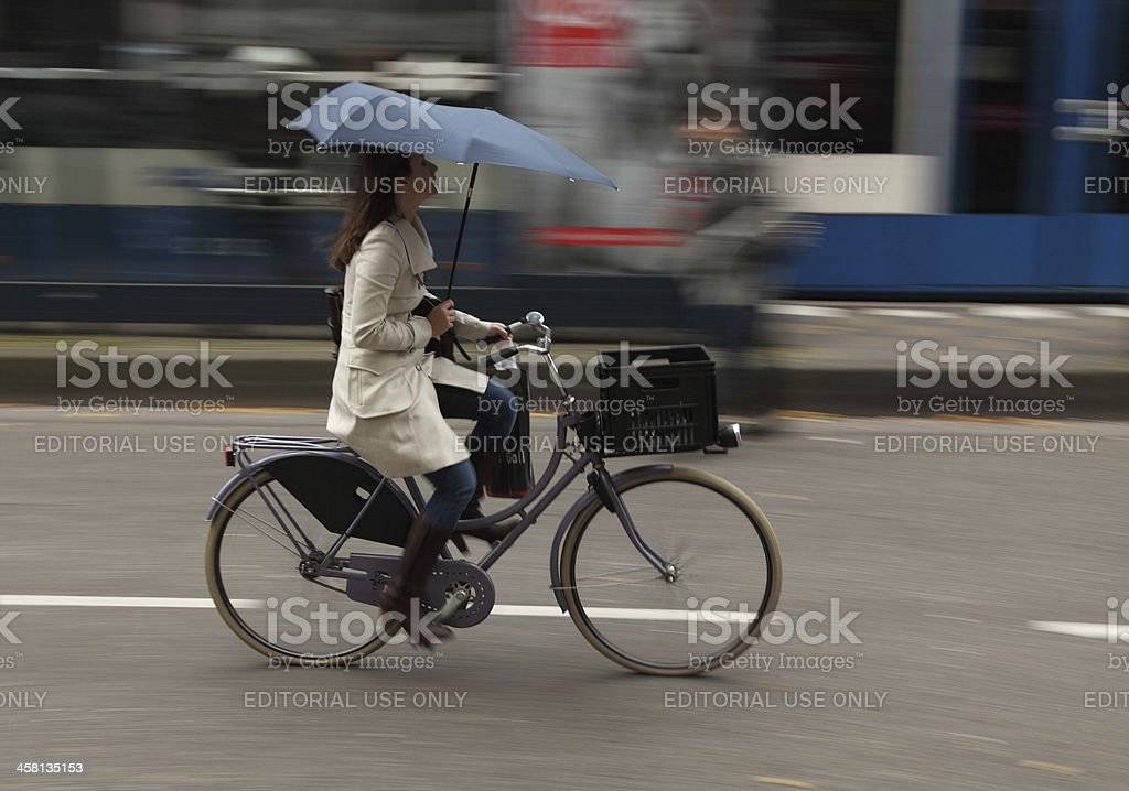 "Woman on bicycle ""Amsterdam,Netherlands- October 30th, 2011:Panning image of a young woman with umbrella riding her bicycle in a street in Amsterdam. Amsterdam is one of the most bicycle-friendly large cities in the world and is a centre of bicycle culture with good facilities for cyclists such as bike paths and bike racks, and several guarded bike storage garages."" Active Lifestyle Stock Photo"