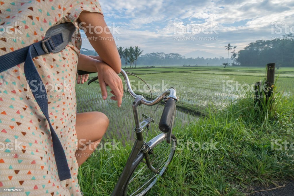 Woman on bicycle stops to admire rice fields, Indonesia stock photo