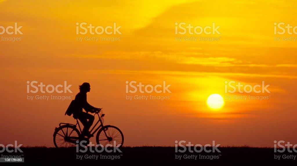 Woman on Bike at Sunrise royalty-free stock photo