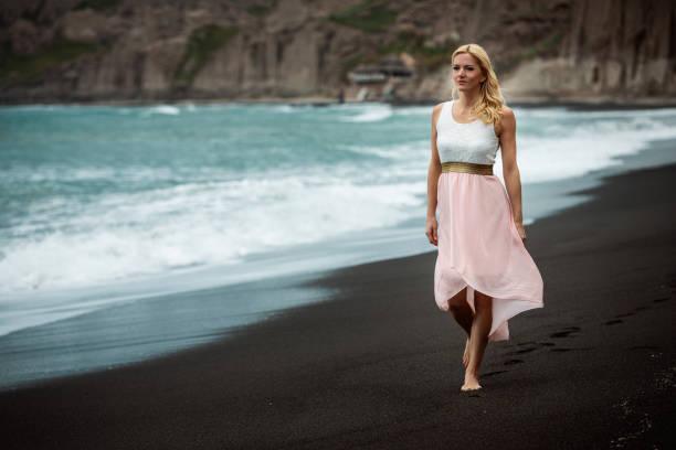Woman on black beach stock photo