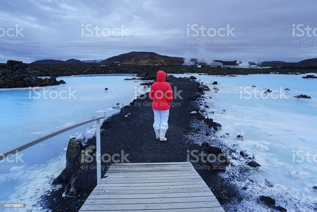 Woman on Black gravel path through blue thermal pools stock photo