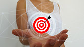 Woman on blurred background using target and arrow on digital interface