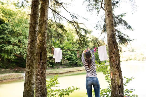 frau auf campingurlaub im wald am see. - horizontal gestreiften vorhängen stock-fotos und bilder