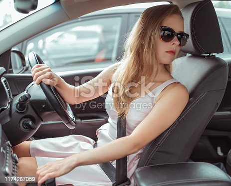istock Woman on car looking back 1174267059