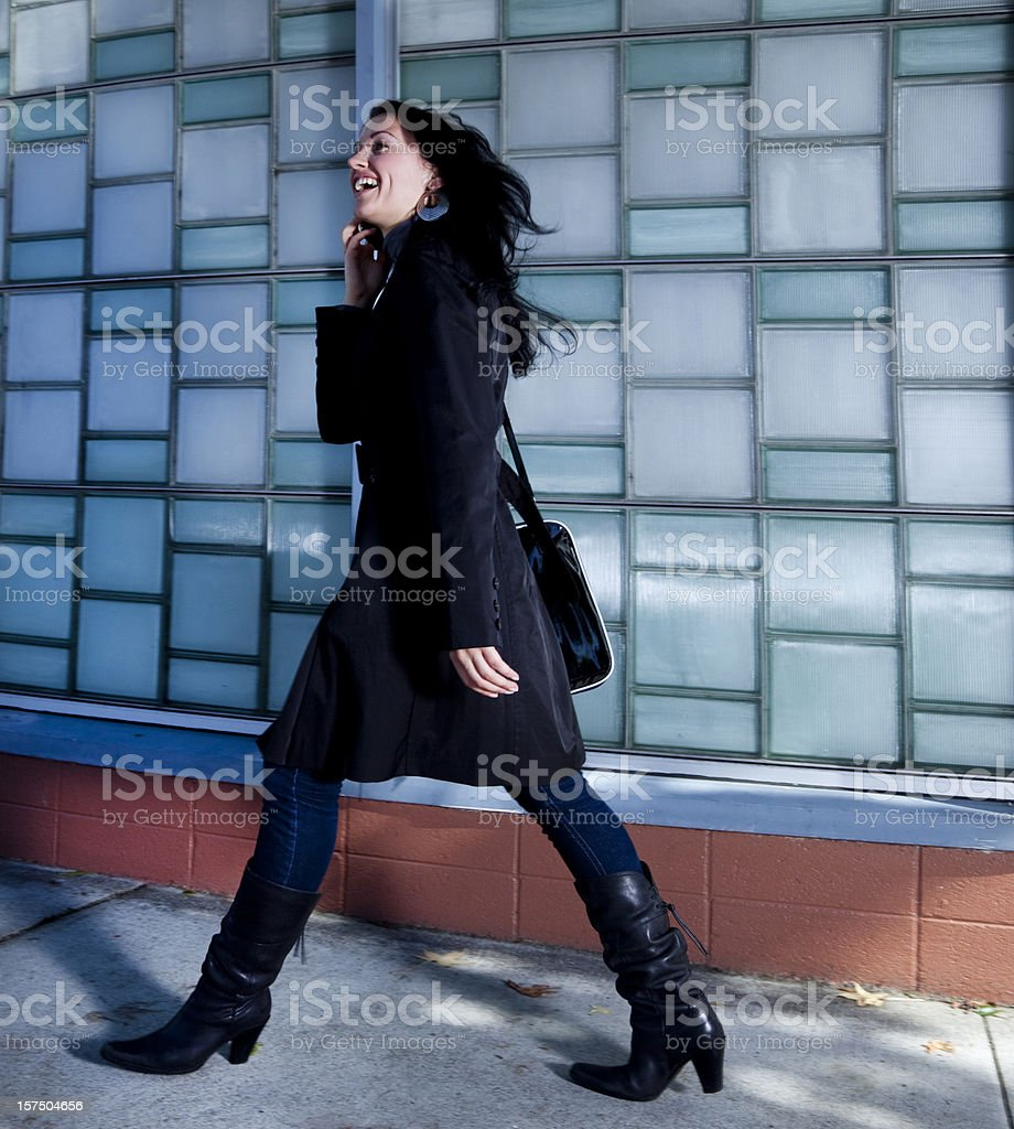 woman on cell phone walking down the street stock photo
