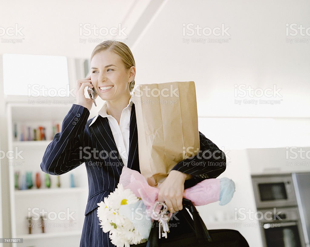 Woman on cell phone with shopping bag and daisies royalty-free stock photo