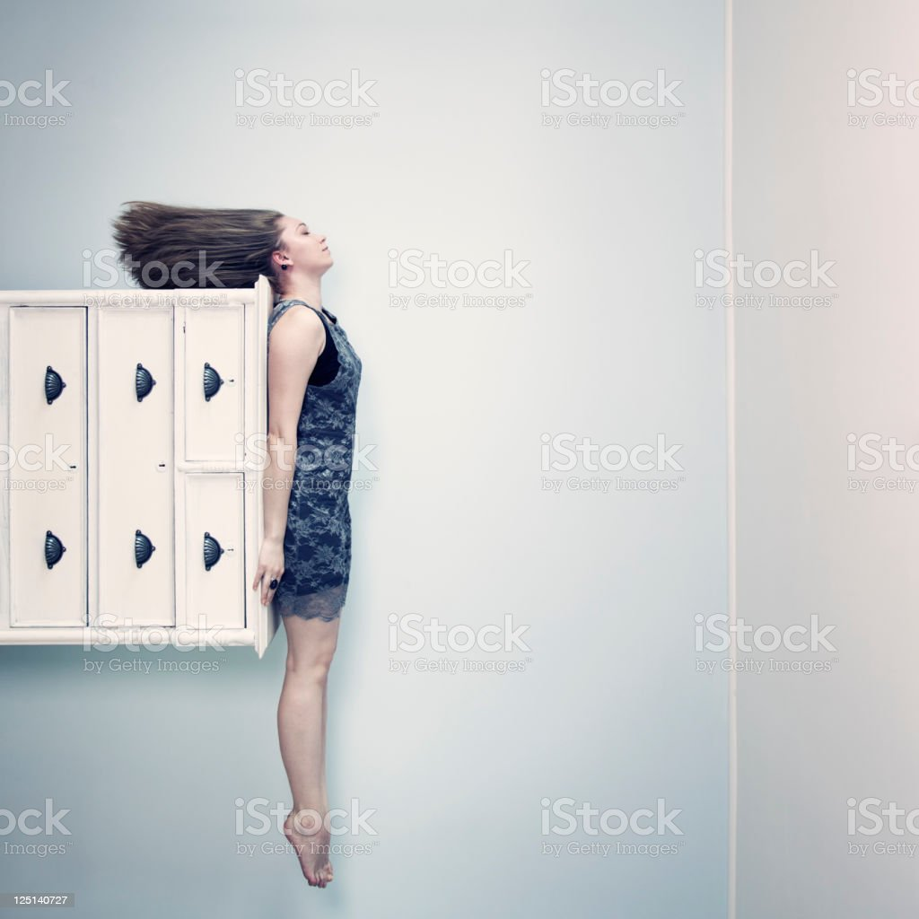 Woman on chest of drawers stock photo