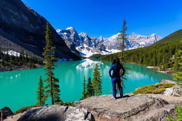 Woman on cliff admiring Moraine Lake and mountains scenic view, Rocky Mountains, Banff National Park, Alberta, Canada Woman on cliff admiring Moraine Lake and mountains scenic view, Rocky Mountains, Banff National Park, Alberta, Canada valley of the ten peaks stock pictures, royalty-free photos & images