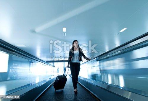 istock Woman on conveyor pulling trolley suitcase 165051663