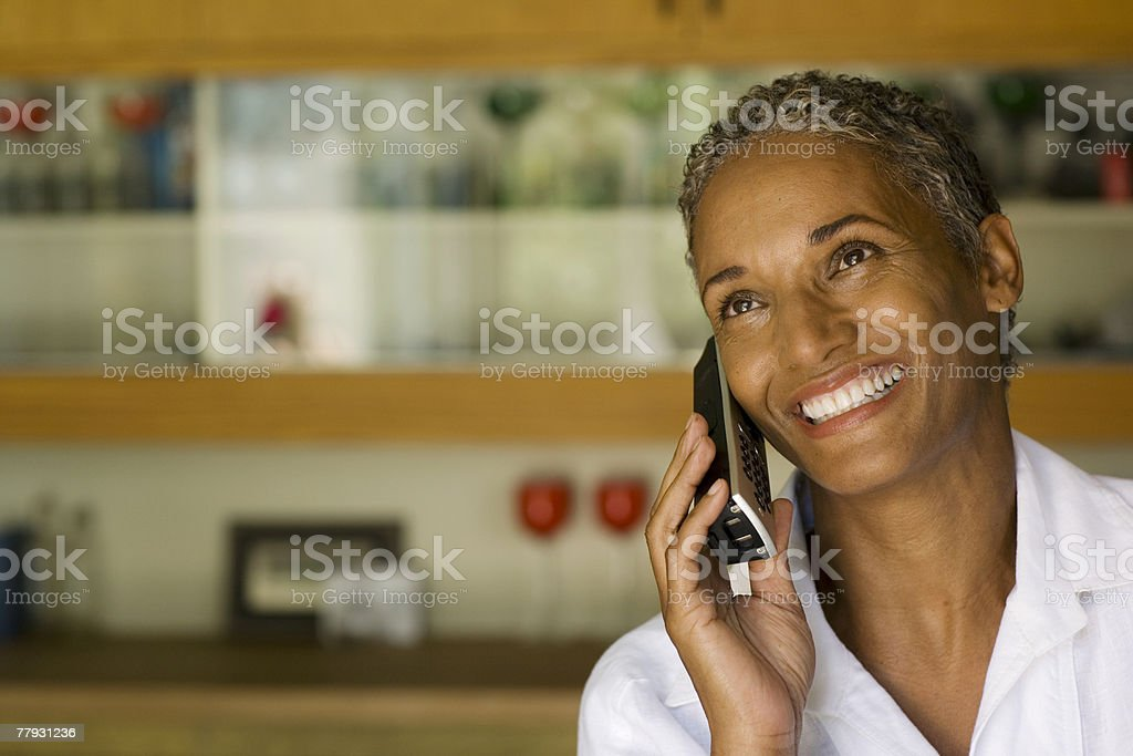 Woman on cordless telephone smiling stock photo