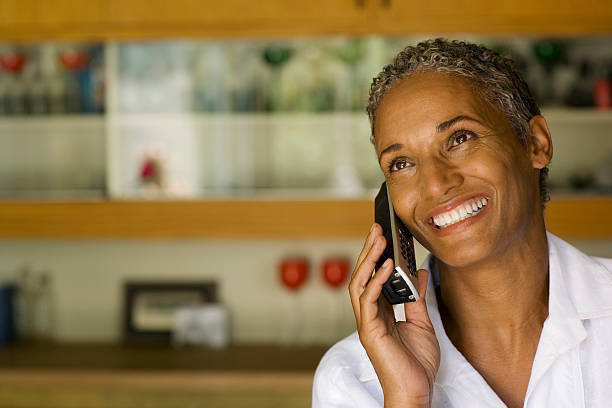 Woman on cordless telephone smiling  cordless phone stock pictures, royalty-free photos & images
