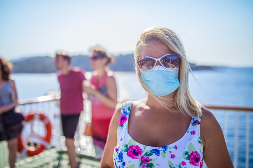 Blonde woman relaxing on cruise ship on summer day during Covid 19 pandemic
