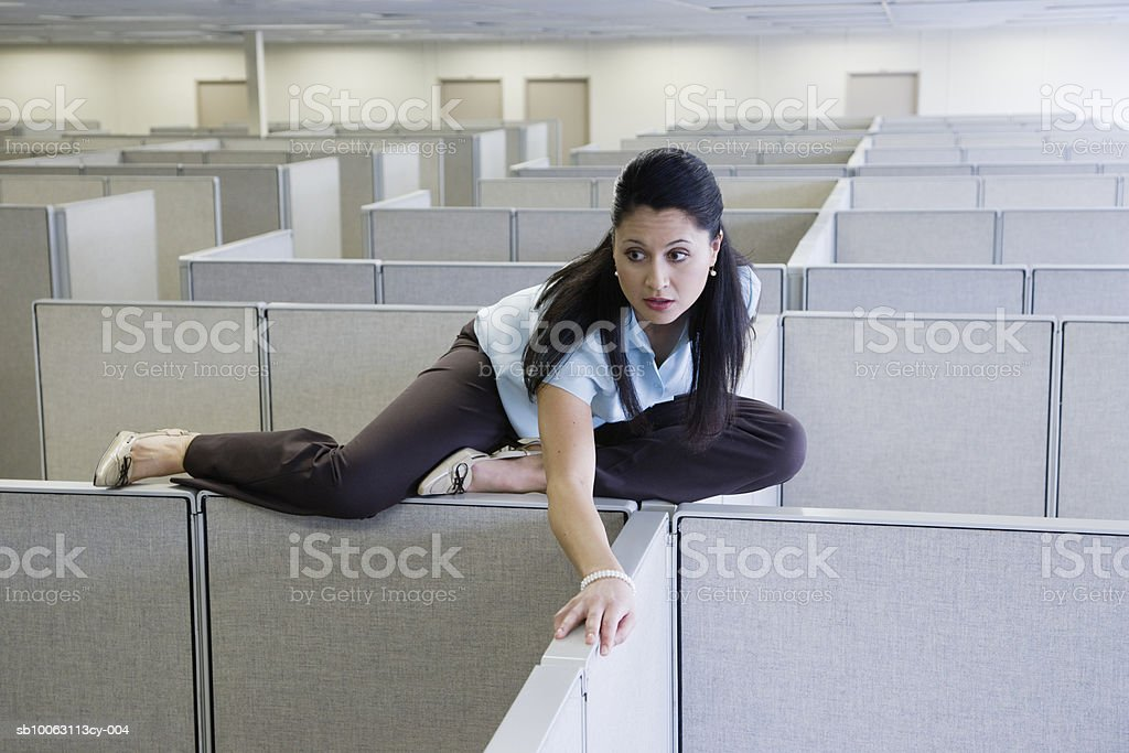 Woman on cubicle wall in office, looking away royalty free stockfoto