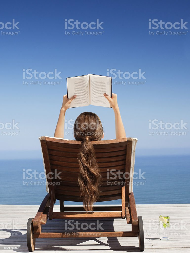 Woman on deck chair reading book stock photo