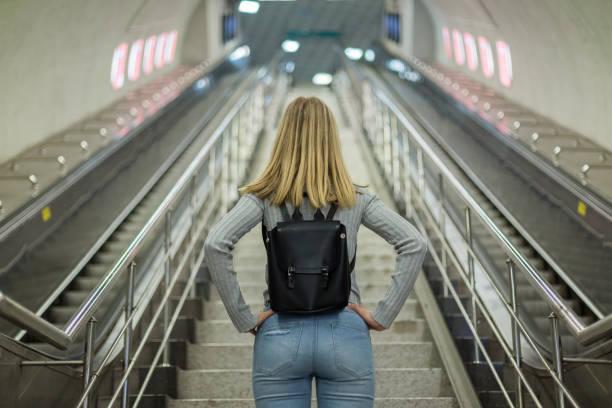 woman on escalator in subway station - escalator foto e immagini stock