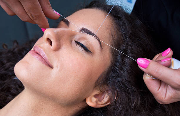 woman on facial hair removal threading procedure attractive woman in beauty salon on facial hair removal eyebrow threading procedure threading stock pictures, royalty-free photos & images