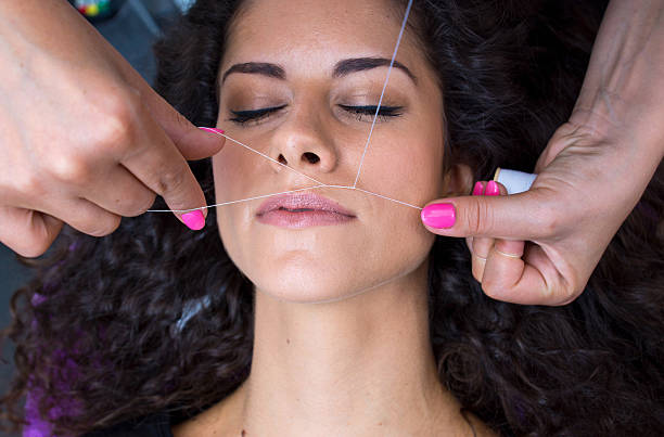 woman on facial hair removal threading procedure attractive woman in beauty salon on facial hair removal threading procedure threading stock pictures, royalty-free photos & images
