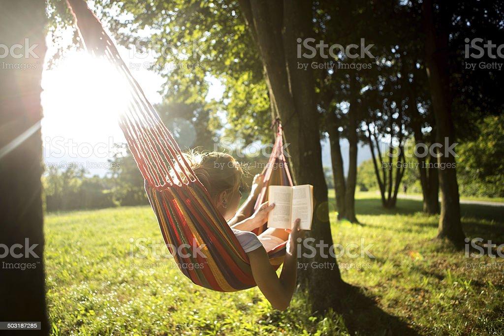 Frau in Hängematte am sunset liest Buch – Foto