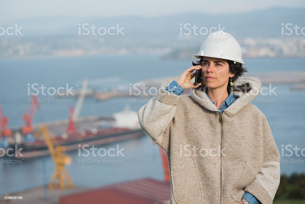 woman on harbor with safety helmet talking on the phone royalty-free stock photo