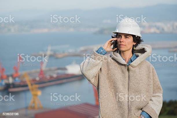 Woman On Harbor With Safety Helmet Talking On The Phone Stock Photo - Download Image Now