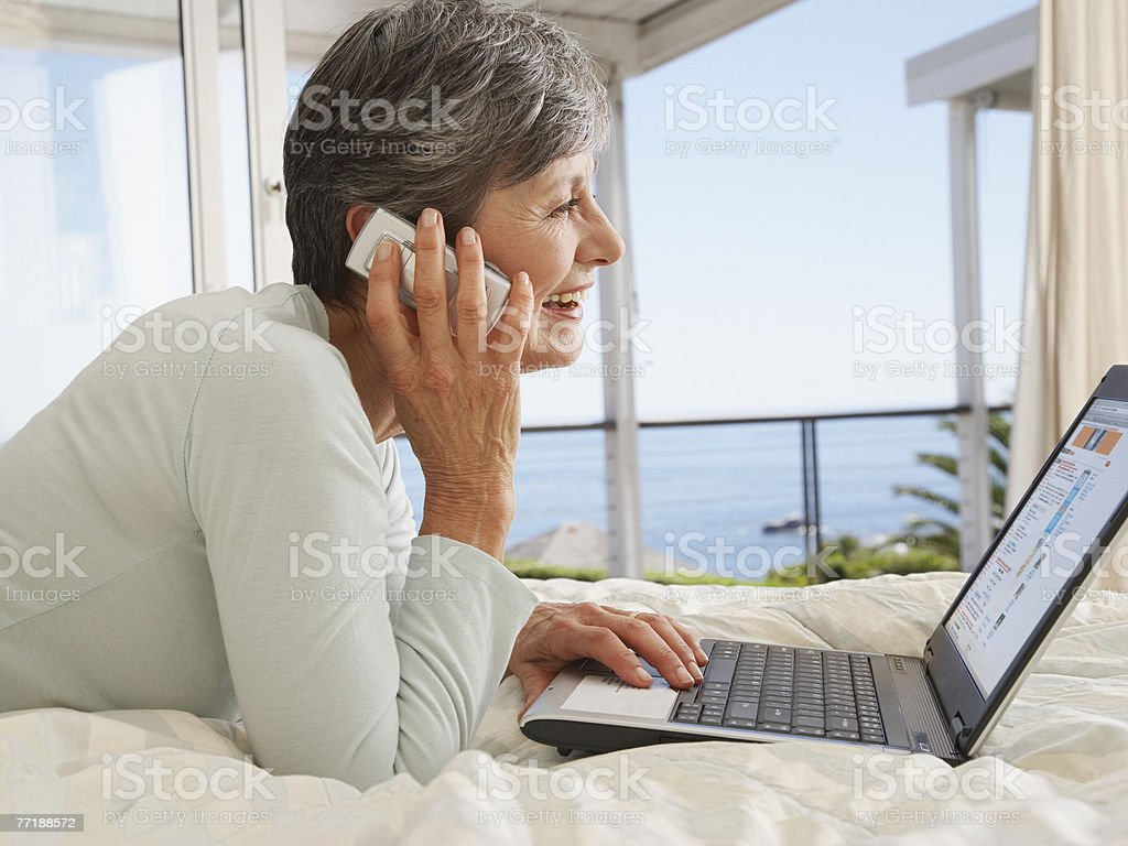A woman on her cellular phone using a laptop royalty-free stock photo