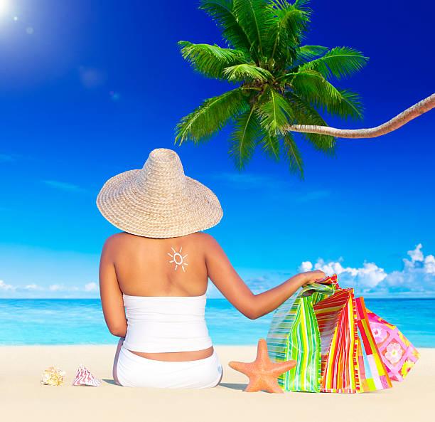 frau im urlaub am strand mit einkaufstaschen - shell tattoos stock-fotos und bilder