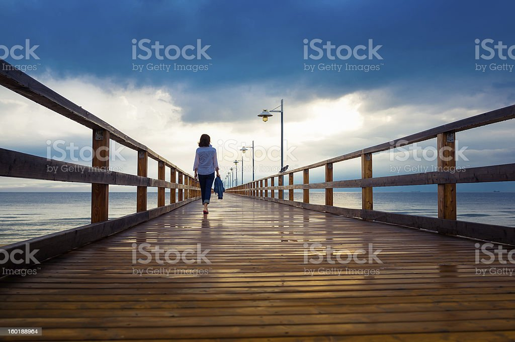Woman on jetty stock photo
