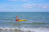 Woman on kayak near beach in a tropical island