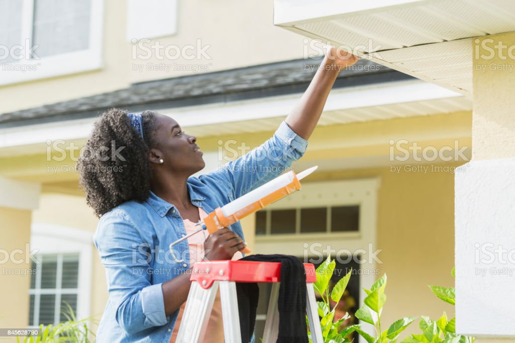 Woman on ladder outside house doing repairs stock photo