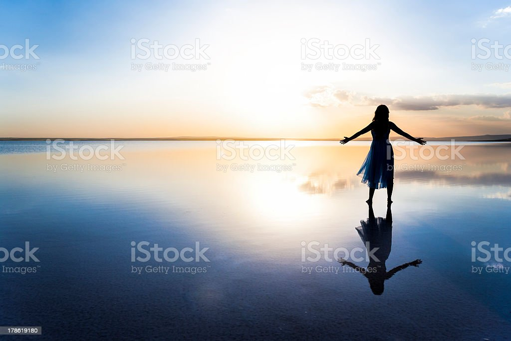 Woman on lake at sunset representing freedom stock photo