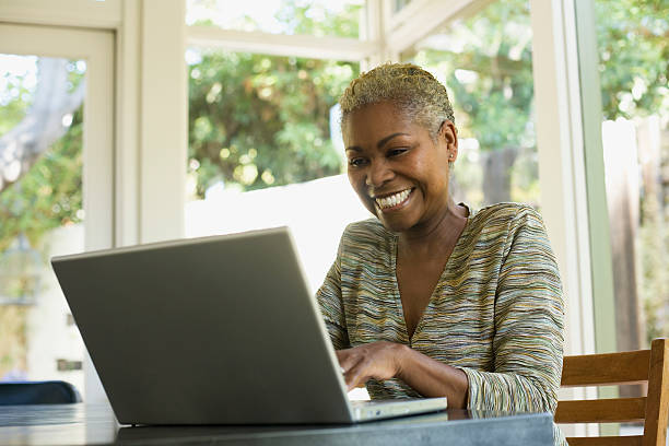 Woman on laptop at a table smiling  one mature woman only stock pictures, royalty-free photos & images
