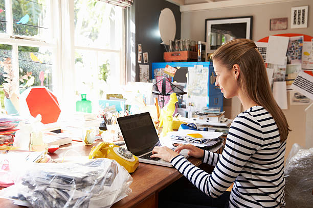 Woman On Laptop Running Business From Home Office Woman On Laptop Running Business From Home Office messy home office stock pictures, royalty-free photos & images