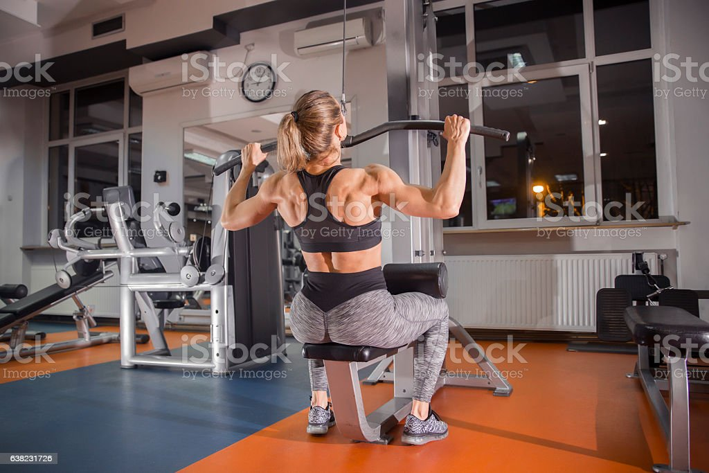 Woman on lat machine in the gym stock photo