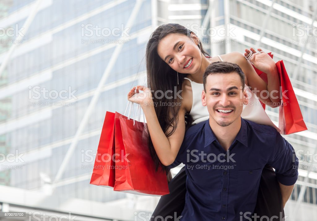 Woman on man's back holding shopping bags with happy feeling, couple shopping concept stock photo