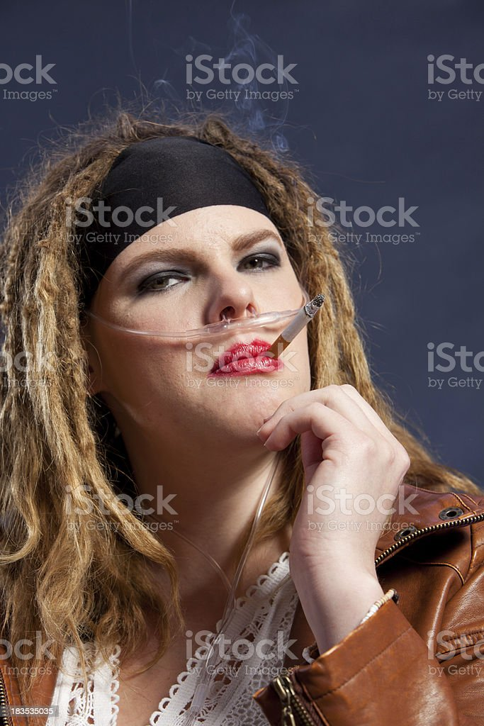 Woman on medical oxygen smoking a cigarette stock photo