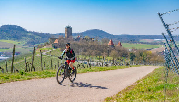 woman on mountain bicycle in vineyard with castle ageless happy senior woman riding her elechtric mountain bike on sunny springtime day in the Vineyards of the Bottwartal with beautiful medieval castle in the background, Heilbronn, Baden-Wuerttemberg electric bike tour stock pictures, royalty-free photos & images